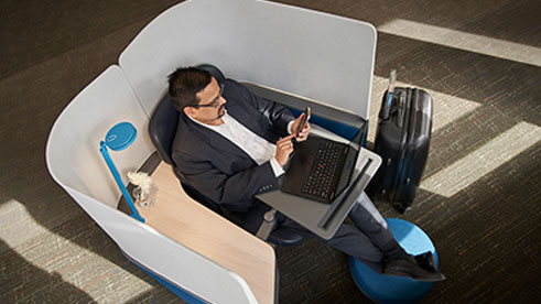 Top-down view of a man in a sport coat kicking his feet up and sitting in privacy table at the airport or hotel typing on his phone. A laptop is on the desk in the kiosk and a suitcase is near his feet.