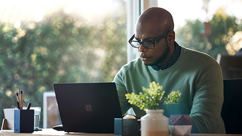 Male working remotely from his home office on Surface Laptop 2 device.